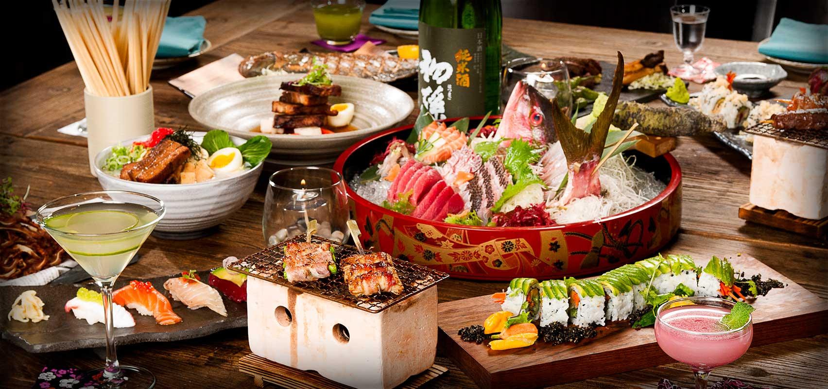 Table with Robata grilled items, sushi, sashimi, sake.