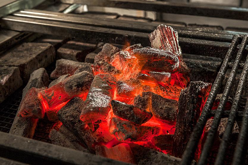 Closeup of glowing binchotan charcoal on a robatayaki grill.